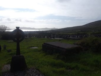Graveyard at Kilmalkedar Church, with a Celtic cross to the left.